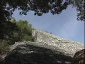 Stock Video Footage of A lone tourist descends the ancient Mayan pyramid in Tulum, Mexico.