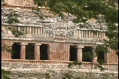 The facade of an ancient Mayan ruin shows the intricate carving and designs used Stock Footage