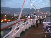 Lights adorn the deck of a cruise ship, as passengers look over the railing at Stock Footage