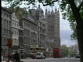 Double decker buses and other automobiles are seen passing Westminster Abbey in Stock Footage