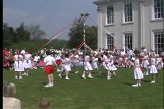 Children dance around a colorful Maypole as they celebrate May Day in Stock Footage