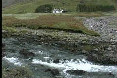 A small creek flows in front of a picturesque cottage in Scotland. Stock Footage