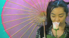 Funny cross eyed Asian girl with rose and umbrella -2 Stock Footage