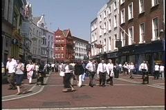 Shoppers and pedestrians walk down a main street in Dublin, Ireland. Stock Footage