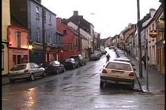 Medium shot of businesses along a rainy street in Dingle, Ireland. Stock Footage