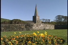 The spire of a cathedral towers over a colorful garder near Struell Wells Stock Footage