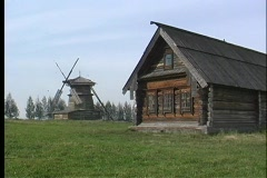 A pan shot of a wooden house and wooden windmill in Russia. Stock Footage