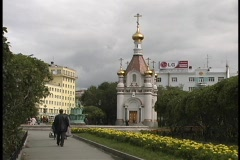 A student walks down a yellow flowered pathway toward Yekaterinburg University Stock Footage
