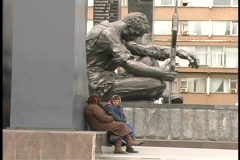 People sit and talk at the base of the Yekaterinburg Afghanistan Memorial Statue Stock Footage