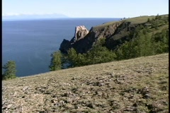 A pan-left of an ocean, viewed from the edge of a steep cliff. Stock Footage