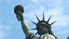 The Statue of Liberty, with torch held high, stands against Stock Footage