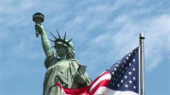 The American flag waves in the foreground with the Statue of Stock Footage