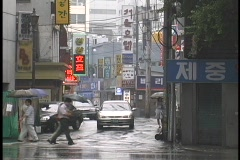 Pedestrians and traffic travel through a rainy intersection in Seoul, South Stock Footage