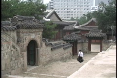A young man carrying a  brief case walks past the Doeksugnung Palace in Seoul, Stock Footage