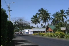 Cars and bikes driving on a city street on Rarotanga one of the Cook Islands in Stock Footage