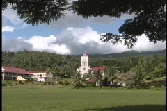 A small village sitting near the hills and trees of an island in the South Stock Footage