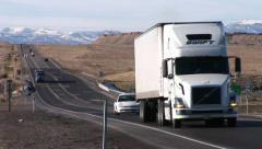 A semi- truck moves along a highway through the Rocky Mountains. Stock Footage