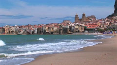 Small waves break near houses along a shoreline in Cefalu, Italy. Stock Footage
