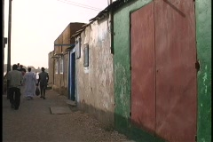 A medium shot of people walking through an alley in a slum in West Africa. Stock Footage