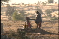 Native South African woman struggles to pump water from a well. - stock footage