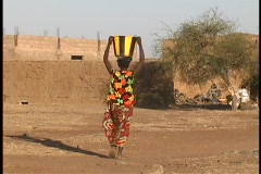 A woman carries a basket with water on her head as she walks through a village Stock Footage
