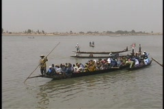 A long ferryboat carries passengers along the shore of the Niger River. Stock Footage