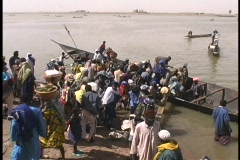 A birds-eye view of passengers leaving a long ferry boat on the muddy shores of Stock Footage