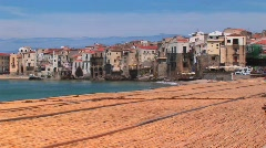 A combed beach near houses along a shoreline in Cefalu, Italy. - stock footage
