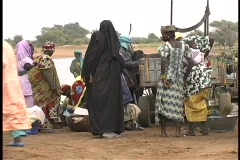 A medium-shot of people gathering along the street for an open market in Mali. Stock Footage