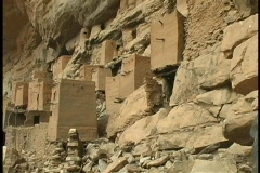 Pan-left along the Tellem Ruins at the base of a large dry mountain range. Stock Footage