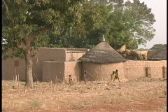 A medium shot of children playing outside the mud huts of Dogon Village in Mali, - stock footage