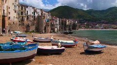 Boats on a beach next to the ocean and houses in Cefalu, Italy. - stock footage