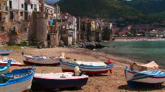 Boats on a beach next to the ocean and houses in Cefalu, Italy. Stock Footage