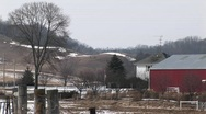 The camera pans an American farm with red barns and silos Stock Footage