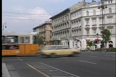 Traffic, trolleys, and trams drive past old buildings in Budapest. Stock Footage