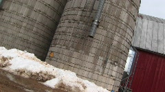 Camera pans up the sides of two grain silos Stock Footage