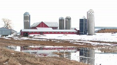 Long-shot of farm barns and silos on a winter's day Stock Footage