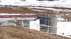 A puddle of melting snow reflects farm buildings and silos Stock Footage
