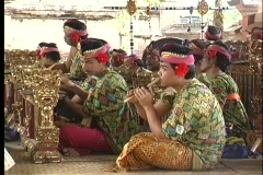 Balinese men playing instruments in an orchestra use a gamelan and flutes. Stock Footage