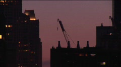 A building crane rests on a rooftop in a golden-hour skyline shot Stock Footage