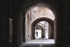 Stock Video Footage of A man stands in a courtyard at the end of several archways in the city of