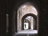 A man stands in a courtyard at the end of several archways in the city of Stock Footage