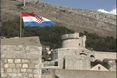A Croatian flag blows in the wind over a castle in Dubrovnik. Stock Footage