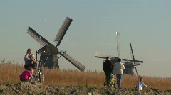 Dutch citizens walk on a footpath in front of windmills, - stock footage