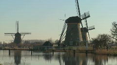 Stock Video Footage of Dutch citizens walk on a bridge in front of windmills.