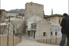 A couple walks down a flight of stairs, toward old stone buildings in Bosnia. Stock Footage