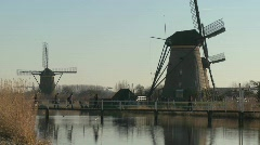 Dutch citizens cross a footbridge in front of windmills along - stock footage