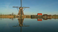 A windmill stands proudly along a canal in Holland. - stock footage