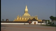 Motorcyclists make their way past the majestic golden Pha That Luang Temple in Stock Footage