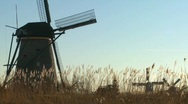 Windmills rise out of the grass in Holland. Stock Footage